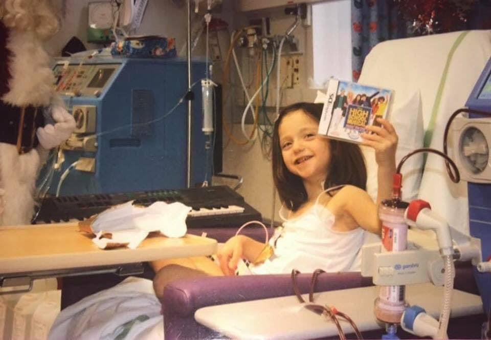This image shows a little girl attached to a big blue dialysis machine.